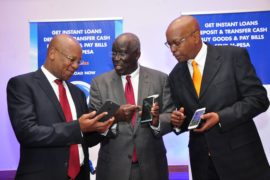 HFC Managing Director Sam Waweru (left) showing HF Group Chairman Steve Mainda (centre) HF Group Managing Director Frank Ireri how to activate the HF Whizz the banks new digital banking solution
