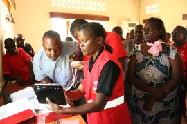 Airtel Kenya CSR manager Aigelgel Murbe installs the data device at Sigweng Karuoth