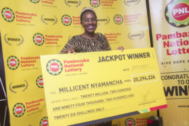 Millicent Nyamancha poses with a dummy cheque of Ksh 20 Million.Millicent became the first Kenya to win the Pambazuka National Lottery Jackpot prize of Ksh 20 million